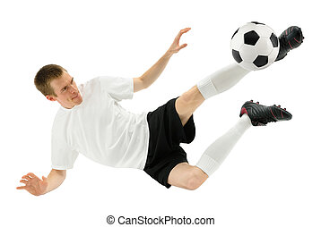 Isolated studio shot of a soccer player kicking the ball in mid-air