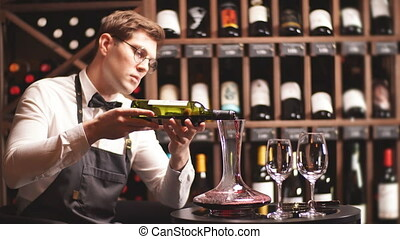 Skilled sommelier pouring wine from decanter ino wine glass....