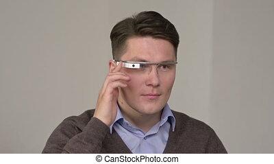 Skilled user - Man using smart glasses against grey...