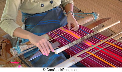 Skilled weaver works colorful patterns into her project in...