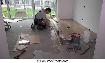 Skilled worker apply glue with trowel on floor for ...