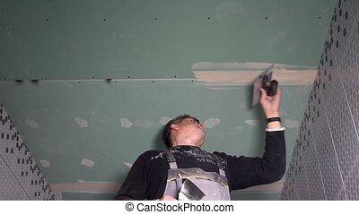 Skilled worker man spackling gypsum plasterboard ceiling ...
