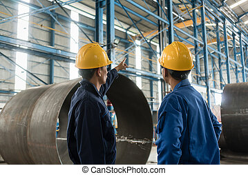 Skilled worker pointing up while giving instructions to an apprentice