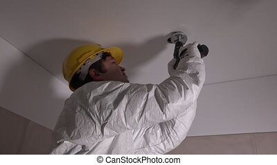 Skilled worker with helmet drilling holes in ceiling....