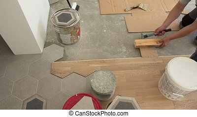 Skilled workers lay parquet floor boards. Man hitting board...