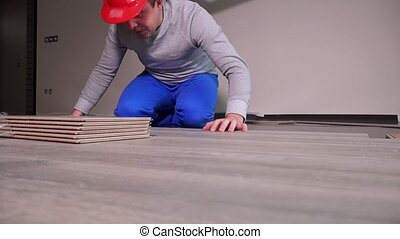 Skilled workers laying wooden oak laminate boards on floor in new room