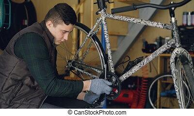 Skilled young man professional mechanic is fixing bike...