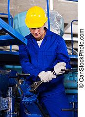 young mechanic repairing factory machine