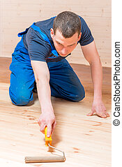 skilled young worker paint roller on a wooden floor in the house