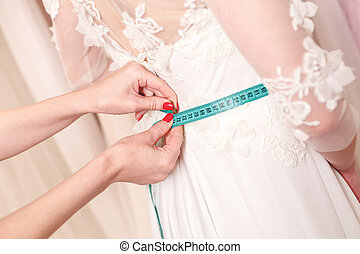 Skillful designer fitting bridal gown to girl - Close up of...