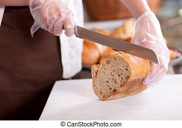 Skillful female baker is serving her customers