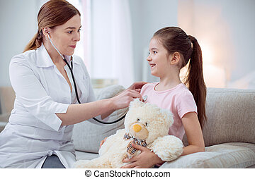 Skillful female doctor checking heart beat