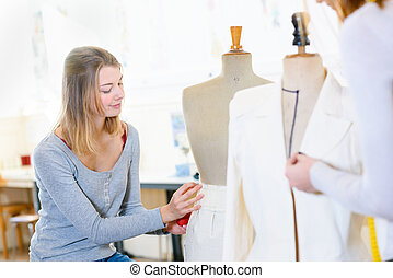 skillful female dressmaking adjusting buttons on clothing