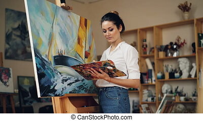 Skillful female painter is working in studio alone painting...