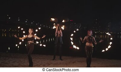 Skillful fireshow artists juggling fire by river - Pretty...