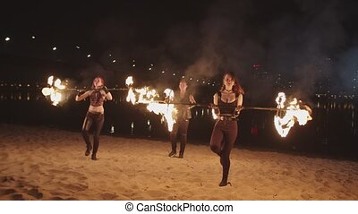 Skillful fireshow artists rolling staves outdoor - Handsome...