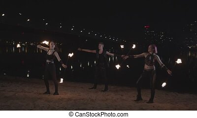 Skillful fireshow performers spinning staves