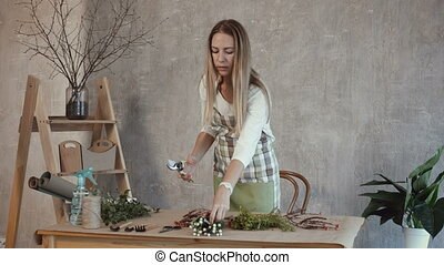 Skillful florist cuts ends of flowers with pruner