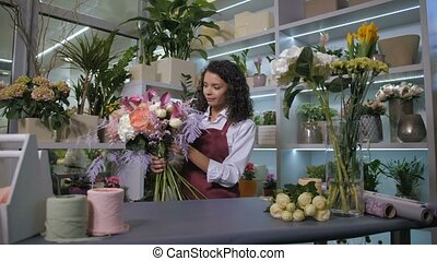Skillful florist finishing bouquet composition - Pretty...