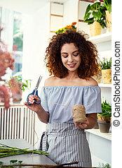 Joyful attractive woman holding scissors