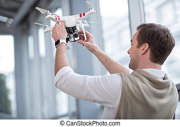 Skillful male freelancer is working with quadrocopter