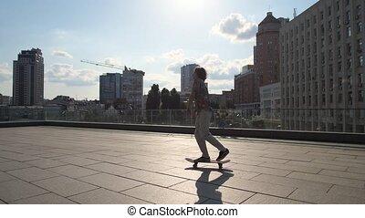 Skillful male skater riding skateboard in city - Side view...