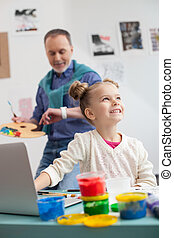 Skillful mature painter and his small granddaughter -...