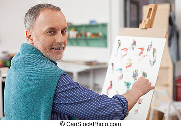 Skillful old artist is painting with joy