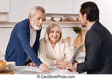 Skillful real estate agent advertising the house to elderly couple