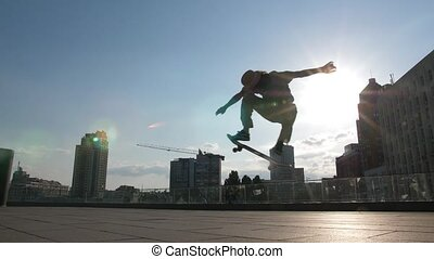 Skillful skateboarder doing ollie trick outdoors - Active...