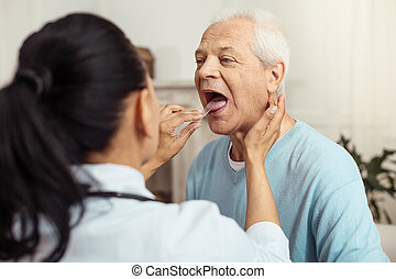 Skillful smart doctor checking her patient - Professional...