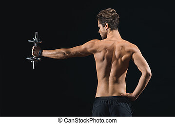 Skillful sportsman exercising with dumbbell