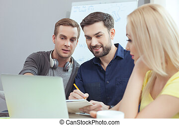 Skillful three workers are working in office