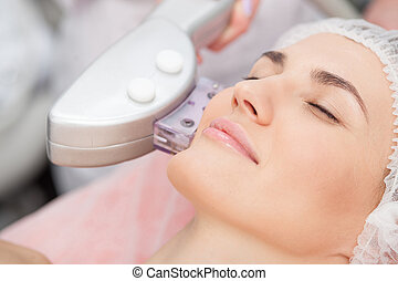 Skillful young cosmetologist is treating female face - Close...