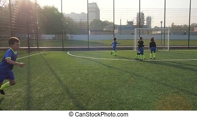 Preteen lucky soccer player successfully hitting penalty shot and scoring goal during football match. Joyful preadolescent footballers rejoicing in goal scored after penalty thanks to skill of forward