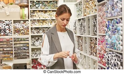 Interested young woman choosing colored buttons for dressmaking in sewing supplies shop
