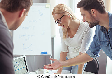 Skillful young team is working with computer