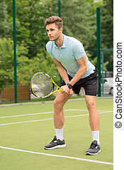 Skillful young tennis player ready to beat ball