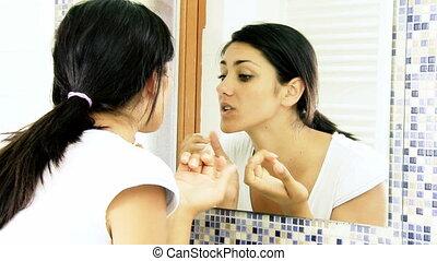 Closeup of beautiful girl looking her facial skin in the mirror.