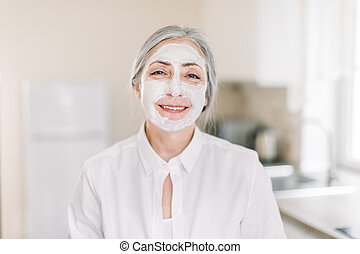 Skin care and anti age beauty treatments, copy space. Indoor shot of beautiful retired grau haired woman with clay moisturizing mask on her face, standing on light kitchen background at home.