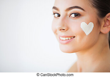 Skin Care. Beautiful model applying cosmetic cream treatment on her face