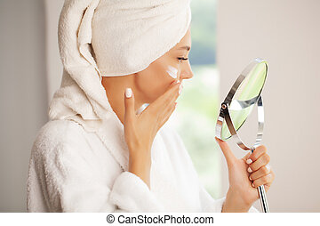 Skin care, beautiful model applying cosmetic cream treatment on her face