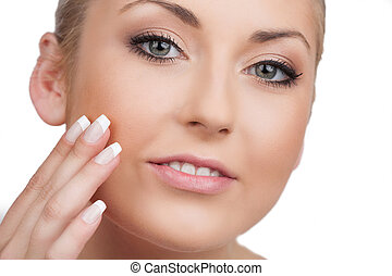 Skin care. Close-up of cheerful woman looking at camera and touching face