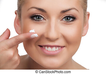 Skin care. Close-up of cheerful woman spreading cream on ...