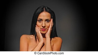 Nude woman with natural make up touching face with pleasure, in spotlight.