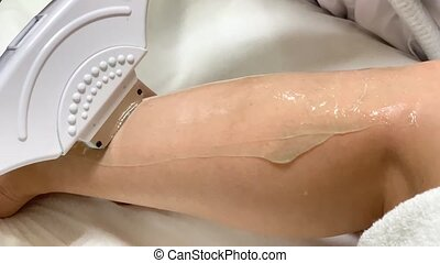 Skin care. Cosmetologist makes laser hair removal on legs.