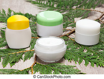 Skin care creams on green plant branch
