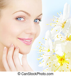 Skin Care. Portrait of young woman and Plum-tree flowers