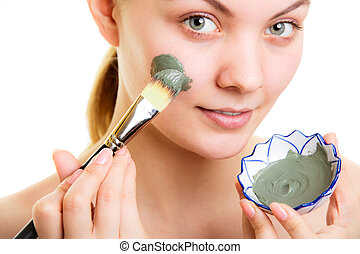 Skin care. Woman applying clay mud mask on face. - Skin...