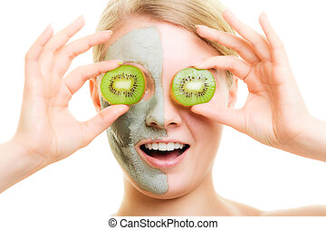 Skin care. Surprised woman in clay mud mask on face covering eyes with slices of kiwi isolated. Girl taking care of dry complexion.